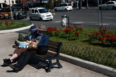 A elderly tourist couple taking a break for the sightseeing near Colosseum